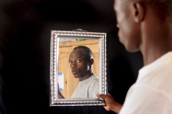 """Self-portrait by Joshua Munyaburanga. Joshua calls this image """"Two Brothers"""" as the boy on the right side of the frame is his brother, Sustain, while the face in the mirror is his own."""
