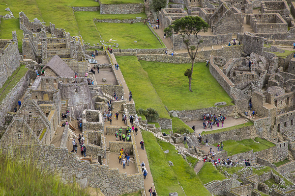 Tourists explore Machu Pichu's stone structure. The number of daily tourists who visit the site relatively unresricted has put the Machu Pichu on the endangered archeological site and the Peruvian government is considering tighter restrictions.