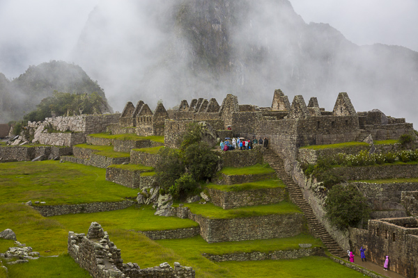 "Visitors explore the ""urban"" or residential areas of Machu Pichu which are built in the lower regions of the city and housed farmers, servants and teachers etc."