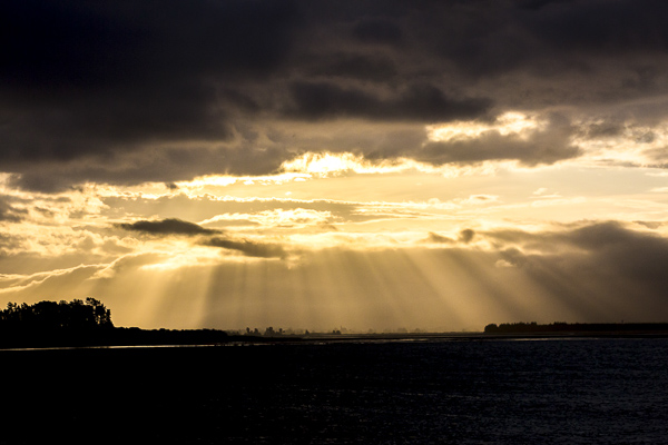 Light is filtered though the clouds at sunset over beautiful Tahanui beach in Nelson, New Zealand.